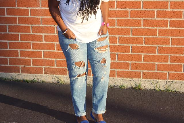 woman in ripped jeans with hands in pockets looking down.